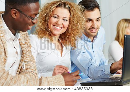 Happy people doing further training in academy course with laptop computer