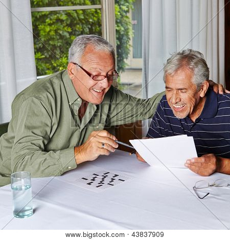 Two happy senior citizens solving riddles in a rest home