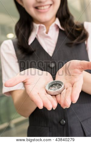 Business woman holding a compass, closeup portrait in city.