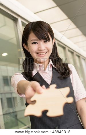 Business woman holding a piece of puzzle, closeup portrait in city.