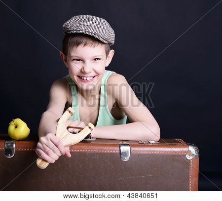 vintage art portrait of little boy looking at camera holding catapult and  leaning on old suitcase, retro stylization of 30-50s