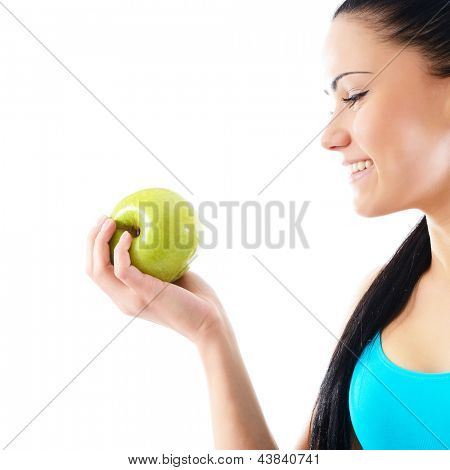 Young happy attractive woman holding green apple and smiling, over white