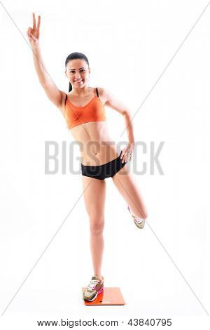 Young woman with scale showing winner gesture happy of weightloss and a healthy slim body, over white