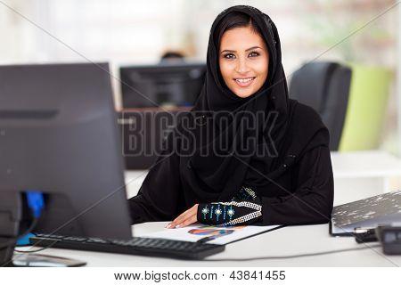empresária de árabe moderna atraente em roupas tradicionais, trabalhando no escritório