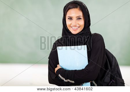 beautiful female middle eastern college student in front of chalkboard