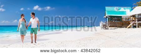 Panorama of a couple on a tropical beach at Caribbean