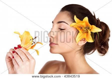 Beautiful Arabic woman with yellow lily flower in head enjoying flower scent, brunette girl with closed eyes isolated on white background, relaxation in day spa, aroma therapy