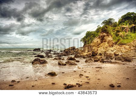Dramatic storm on the beach of Costa Rica, Manuel Antonio national park, Central America, sandy coastline, dark cloudy sky above rainforest, beautiful landscape of tropical nature