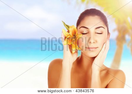 Beautiful woman on the beach with yellow lily flower, Arabic female with closed eyes enjoying day spa, beauty treatment, body care, luxury tropical resort, vacation and travel concept
