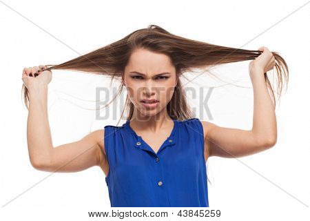 Misunderstanded girl holds her hair in hands isolated over white background