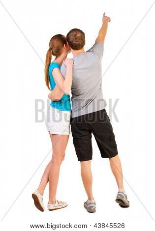 Back view of young couple pointing (woman and man). newlyweds on their honeymoon. . Rear view people collection.   backside view of person.  Isolated over white background.