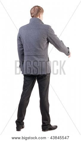 back view of businessman in coat reaches out to shake hands. secured a man who welcomes you. Rear view people collection. backside view of person. Isolated over white background.