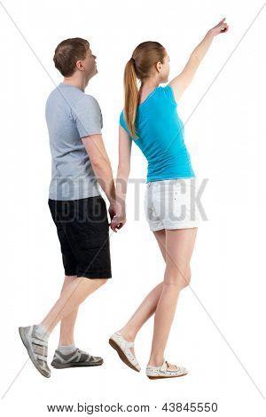 Vista traseira do pé apontando jovem casal (homem e mulher). esposa mostra sua soberba marido curioso