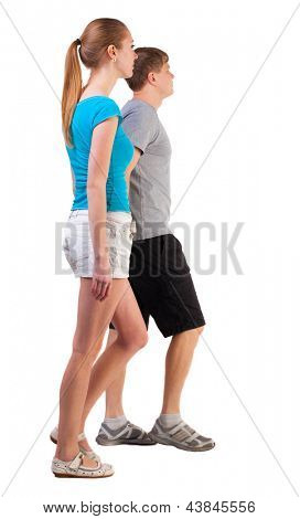 Back view going young couple (man and woman). walking beautiful friendly girl and guy in shorts together. Rear view people collection.  ne backside view of person.  Isolated over white background.