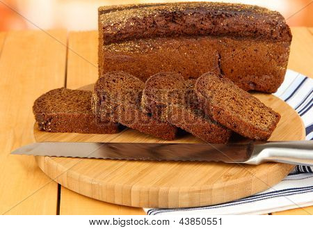 Sliced black bread and knife on chopping board on wooden table close up