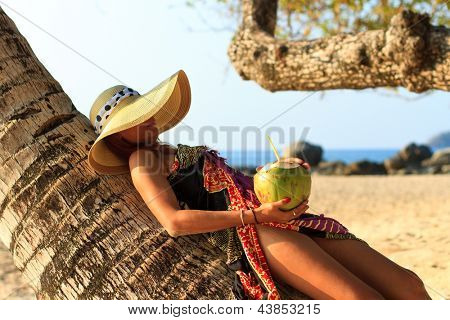 Woman in sarong on a coconut tree holding a cocktail at the  beach  in Thailand