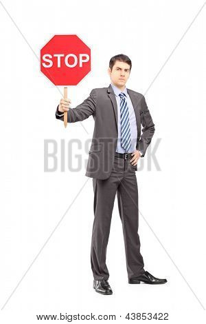 Full length portrait of a businessman holding a stop sign isolated against white background
