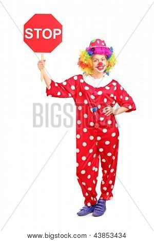 Full length portrait of a clown holding a stop sign isolated against white background