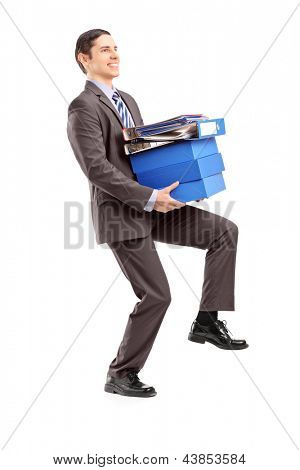 Full length portrait of a young businessman carrying heavy folders isolated on white background