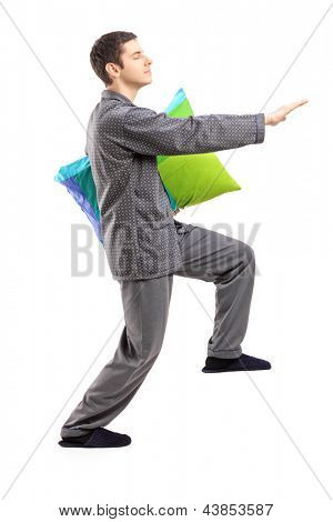 Full length portrait of a man in pajamas sleepwalking with a pillow in his hand isolated on white background