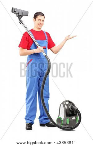 Full length portrait of a young man with a vacuum cleaner gesturing with his hand isolated on white background