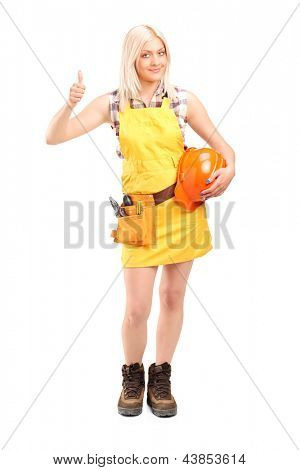 Full length portrait of a female construction worker with equipment giving thumb up isolated on white background