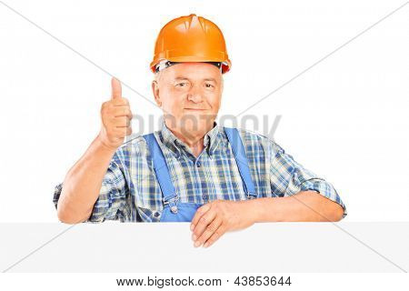 Mature worker with helmet posing behind a panel with thumb up isolated on white background