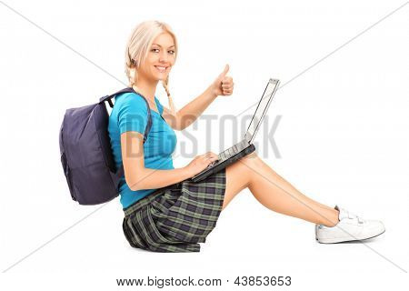 Blond female student working on a laptop and sitting on a floor with thumb up, isolated on white background