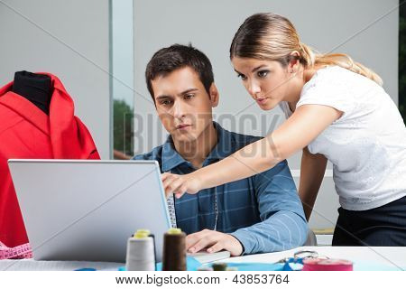 Young male and female fashion designers working on laptop together