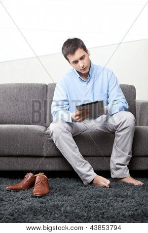 Young man using digital tablet at home on couch.