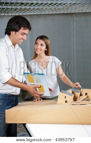 Young male architect looking at model house while female colleague smiling at him