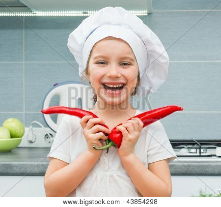 little funny girl in a cap chef in the kitchen with Pepper