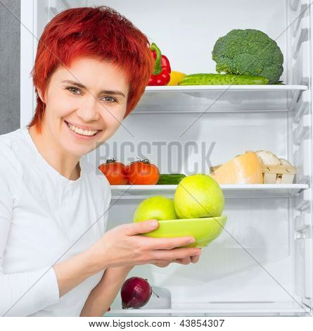 young woman with apples against the refrigerator with food