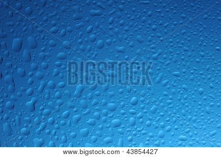 Water drops on blue glass surface