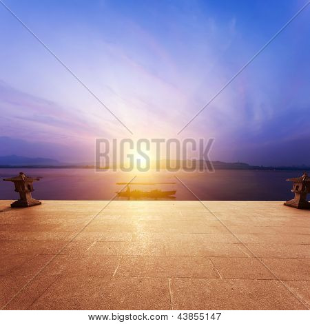 floor beside lake with sunset
