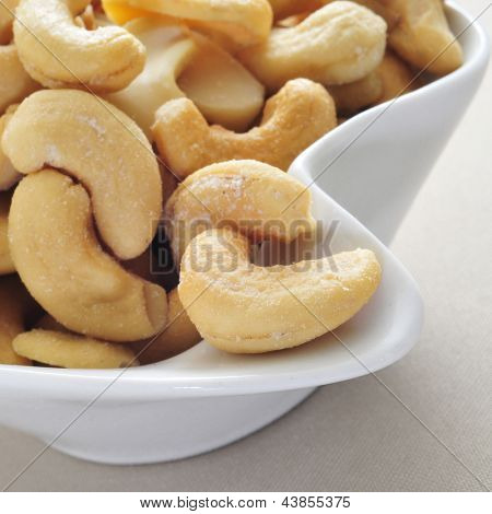closeup of a bowl with roasted and salted cashews on a beige tablecloth