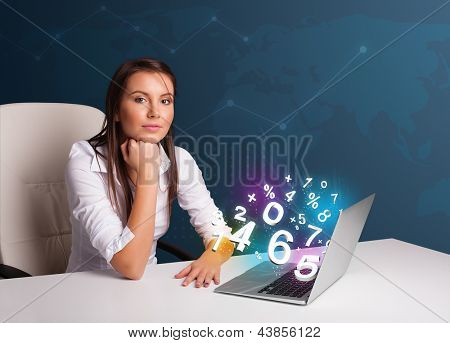 Beautiful young woman sitting at desk and typing on laptop with 3d numbers comming out