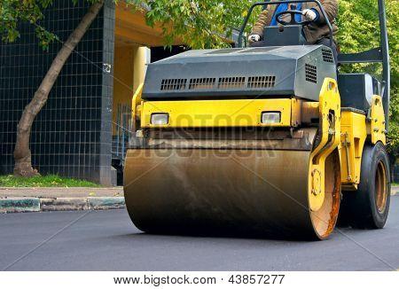 Reparación de la carretera, compactador pone asfalto.