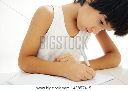 Boy writing on paper at his school and doing schoolwork