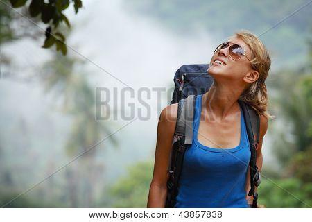 Joven turista con mochila caminando en el bosque tropical