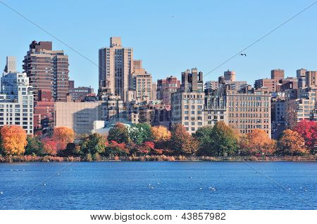 Central Park Autumn with New York City Manhattan Midtown skyline skyscrapers over lake with colorful foliage and clear blue sky.