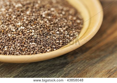bowl of chia seeds on wood surface - a close-up with a shallow depth of field