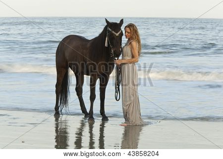 woman in formal dress in ocean with horse, time exposure showing motion of waves