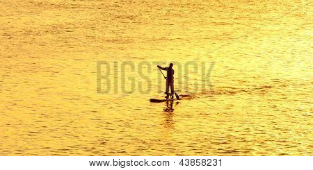 man paddleboarding at sunset with dog