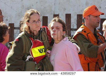 ASHKELON, ISRAEL - JANUARY 10: An unidentified Israeli soldier from rescue team hugs a young unidentified girl who was witness of missile explosion launched by Hamas terrorists from Gaza in Ashkelon, Israel on January 10, 2009.