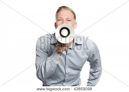 Great news: Young joyful businessman shouting with megaphone isolated on white background.