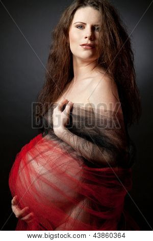 Young beautiful pregnant woman with long curly hair.
