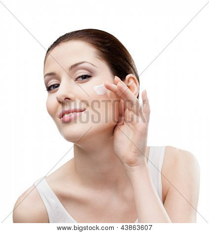 Woman putting on cream on her face, isolated on white. The pursuit of beauty