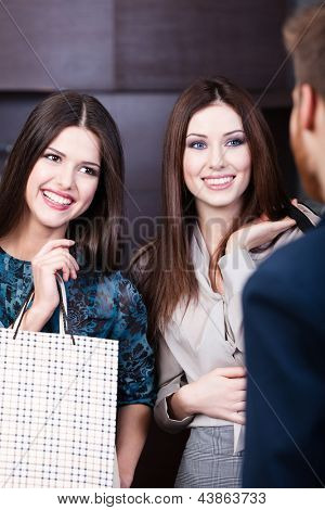 Two girls speak to shop assistant