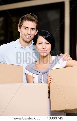 Pareja feliz llevando paquetes de cartón mientras se mueve a la casa nueva